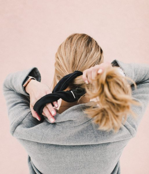 woman tying her hair in black scrunchie