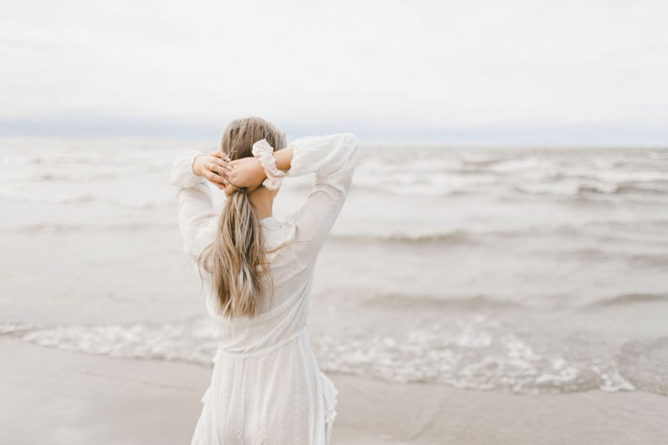 tying up hair with a scrunchie, at a beach