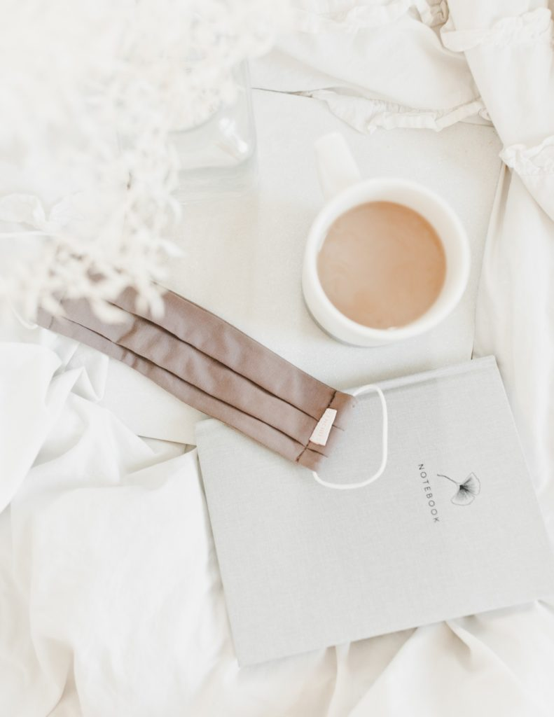 beautiful neutral face mask, coffee and notebook