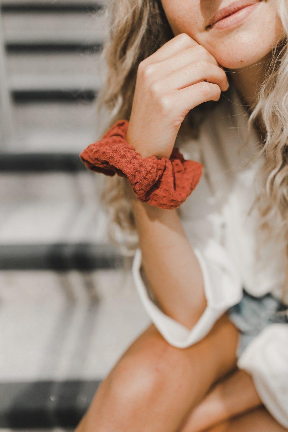 woman with burnt orange scrunchie on wrist